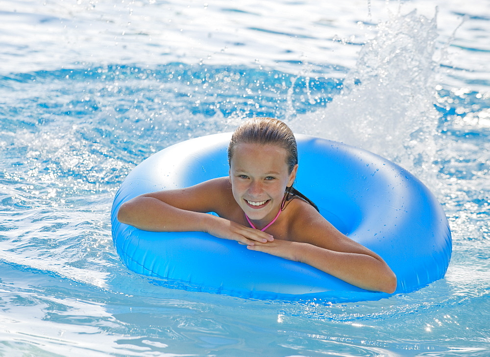 Girl playing with inflatable tube in swimming pool