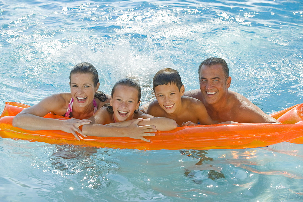 Family resting on raft in swimming pool