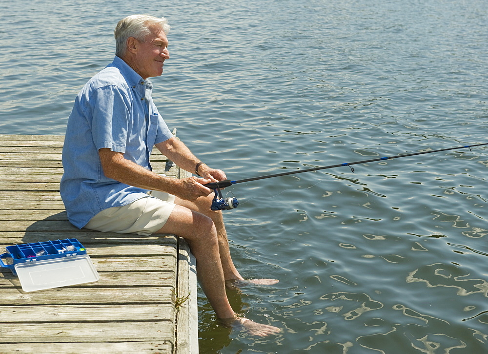Senior man fishing off dock