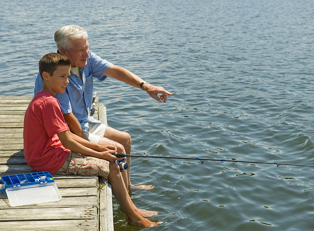 Grandfather and grandson fishing off dock