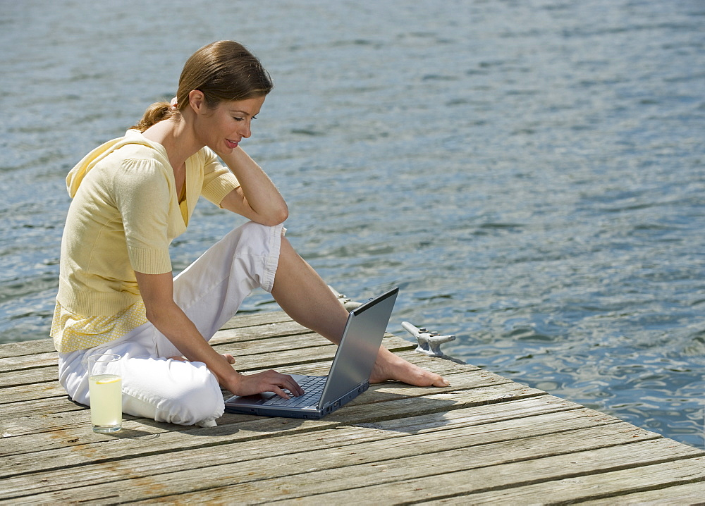 Woman using laptop on dock