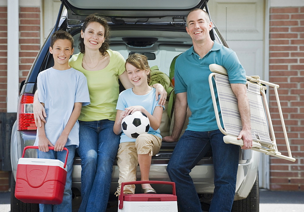 Family holding coolers and beach chair behind car