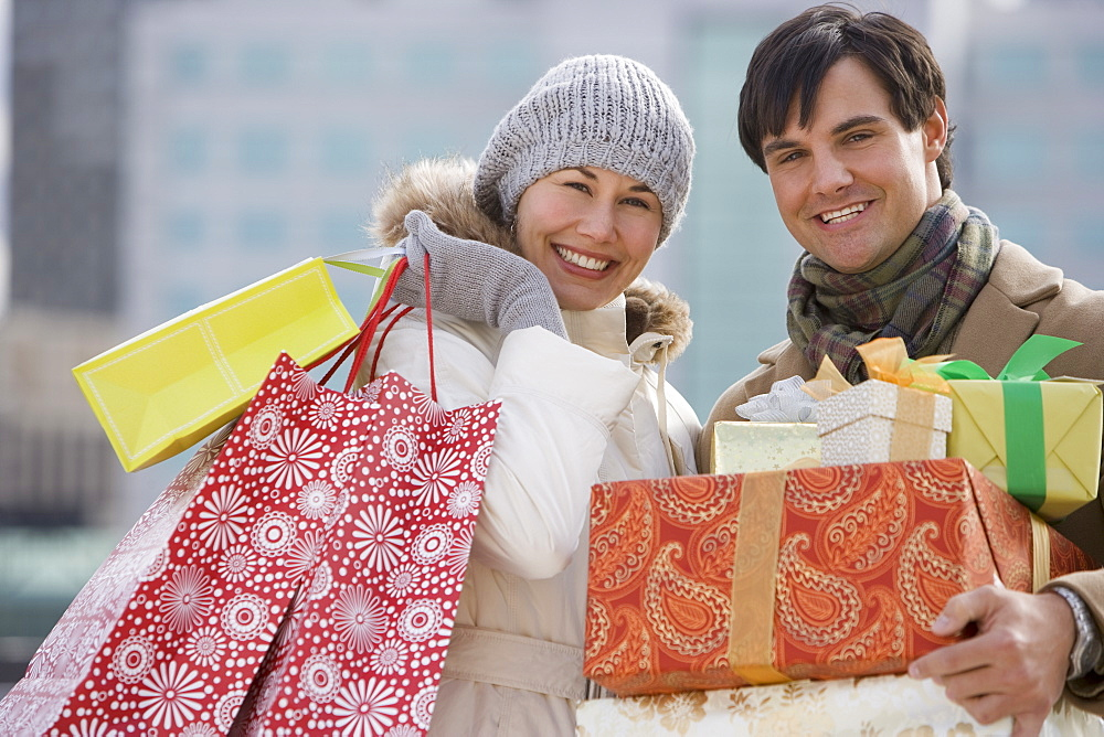 Couple carrying shopping bags and gifts