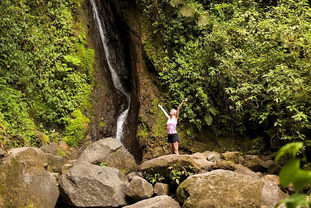 Woman under waterfall, Costa Rica