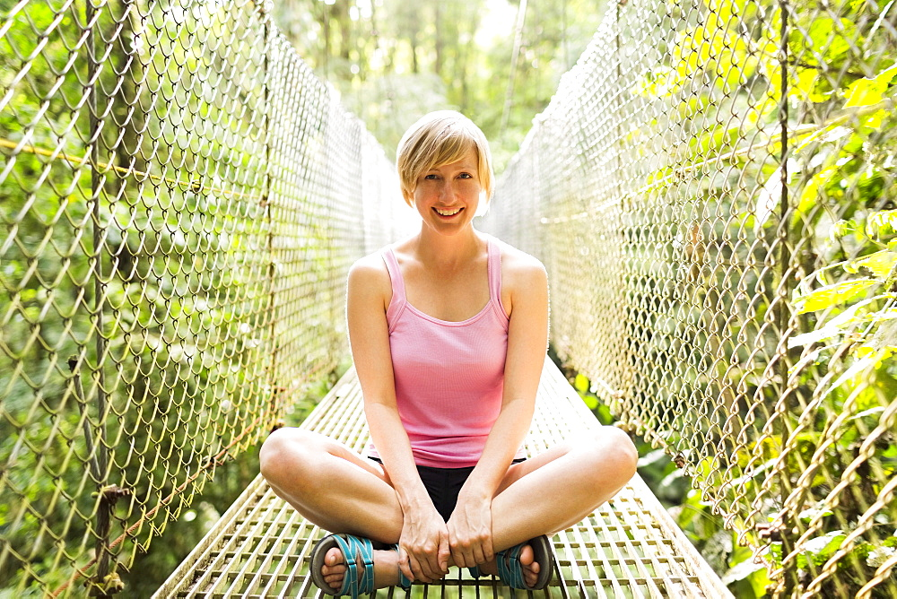Woman sitting with legs crossed and smiling to camera on footbridge in forest, Costa Rica