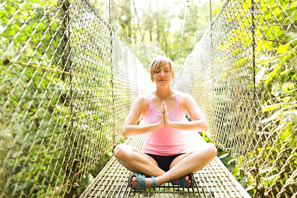 Woman practicing yoga on footbridge in forest, Costa Rica