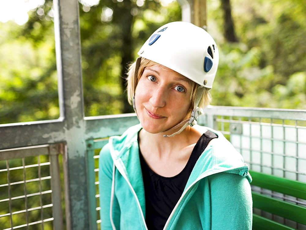 Woman in protective helmet and sitting at net elevator looking at camera, Costa Rica