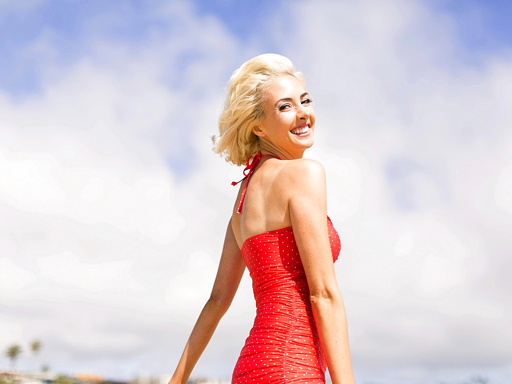 Woman wearing red one piece swimsuit posing to camera