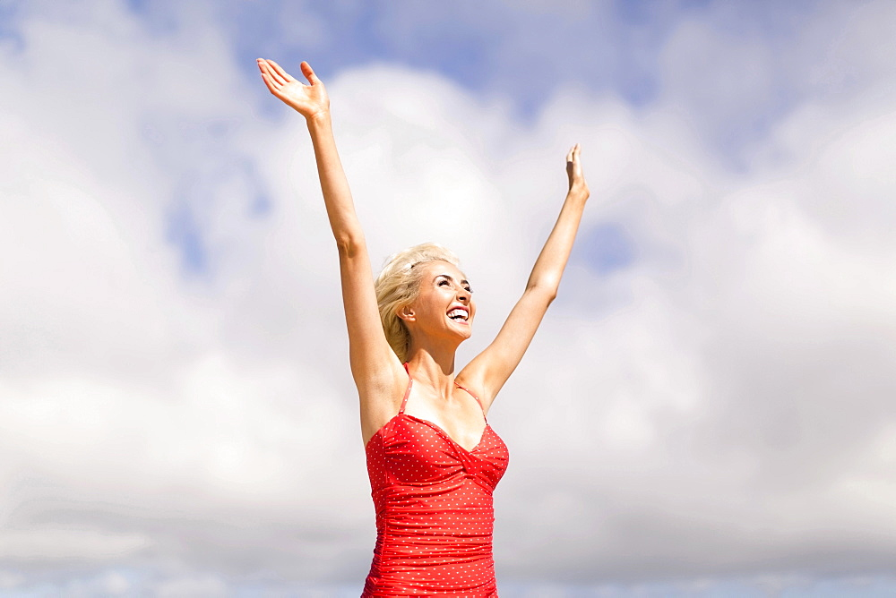 Woman wearing red one piece swimsuit rising arms and smiling