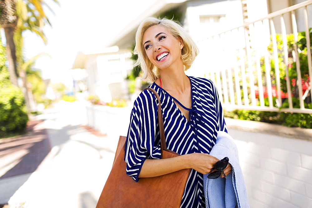 Woman wearing striped blouse walking street and smiling, Costa Mesa, California