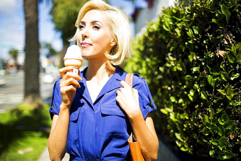 Woman walking with ice-cream, Costa Mesa, California