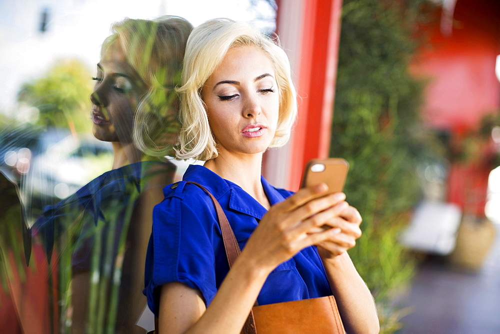 Woman leaning against window and using phone, Costa Mesa, California