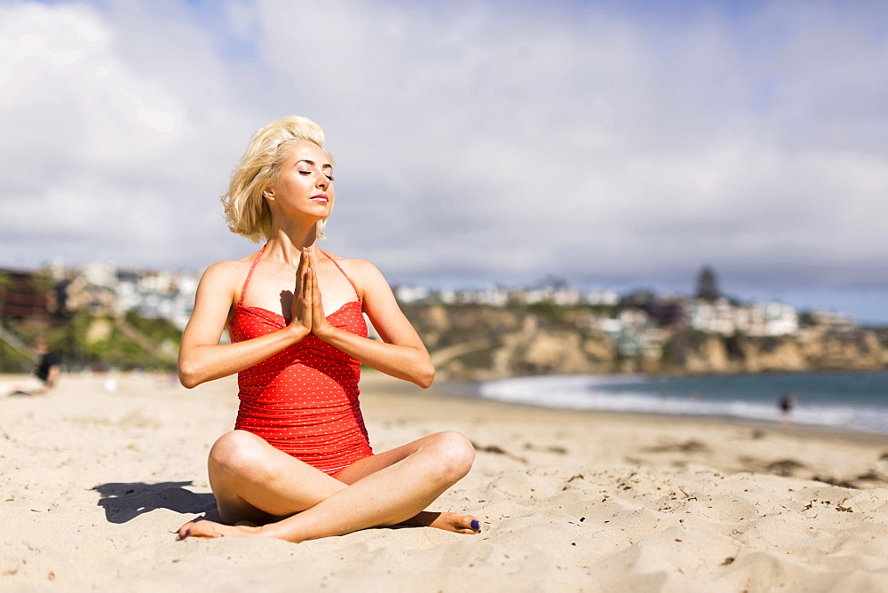Portrait of blond woman on beach practicing yoga, Costa Mesa, California