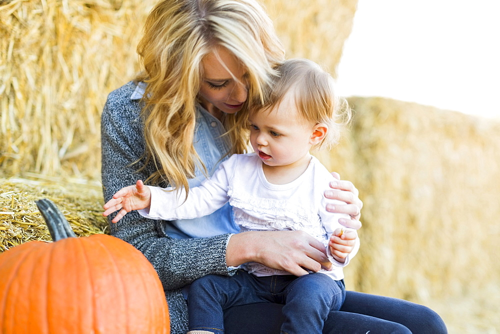 Mother and daughter (12-17 months) looking at large pumpkin