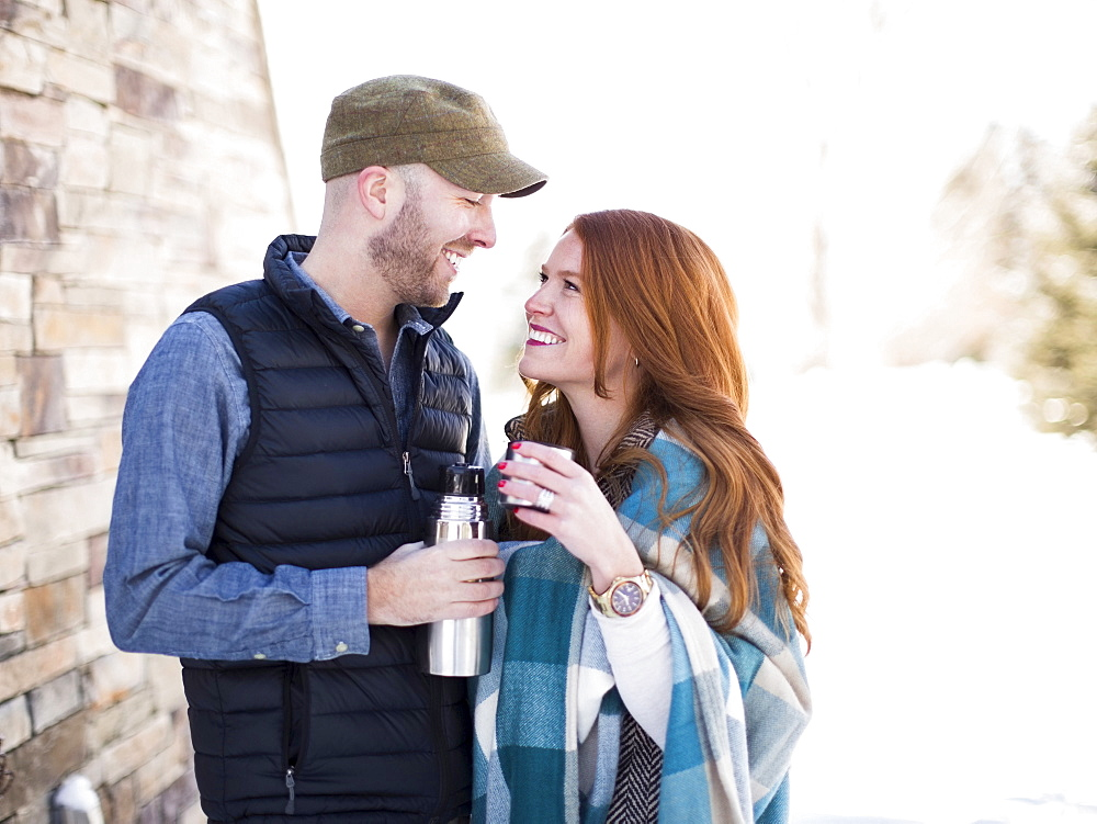 Mid adult couple looking face to face and having drink from vacuum flask
