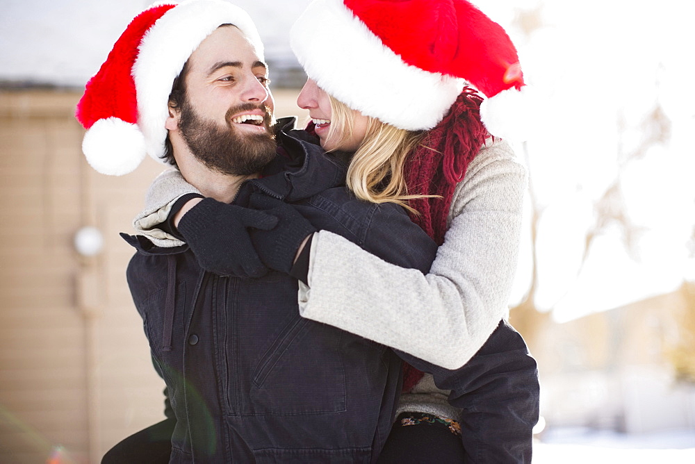 Young couple in santa hats, piggyback