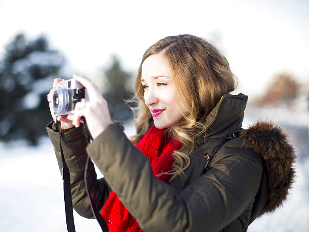 Woman photographing winter landscape