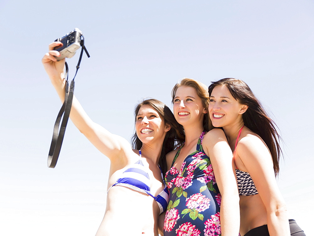 Portrait of three women photographing themselves