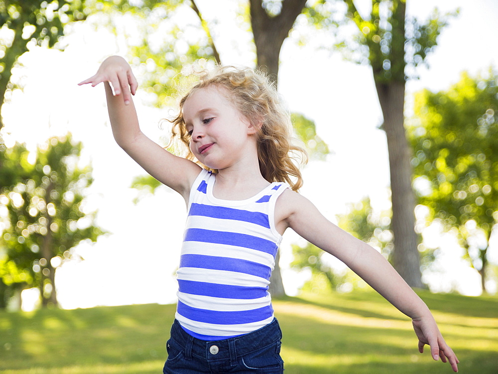Blonde girl (4-5) dancing in park, USA, Utah, Salt Lake City