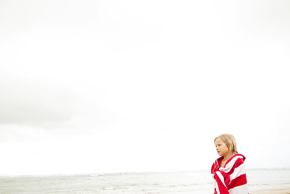 Boy (6-7) wrapped in towel on beach, Kauai, Hawaii
