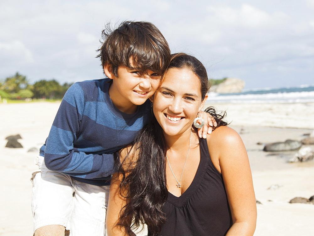 Portrait of boy (10-11) sitting on beach with mother, Kauai, Hawaii
