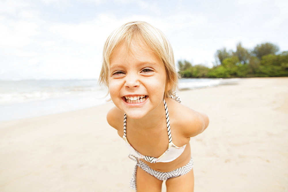 Smiling girl (2-3) on sandy beach, Kauai, Hawaii