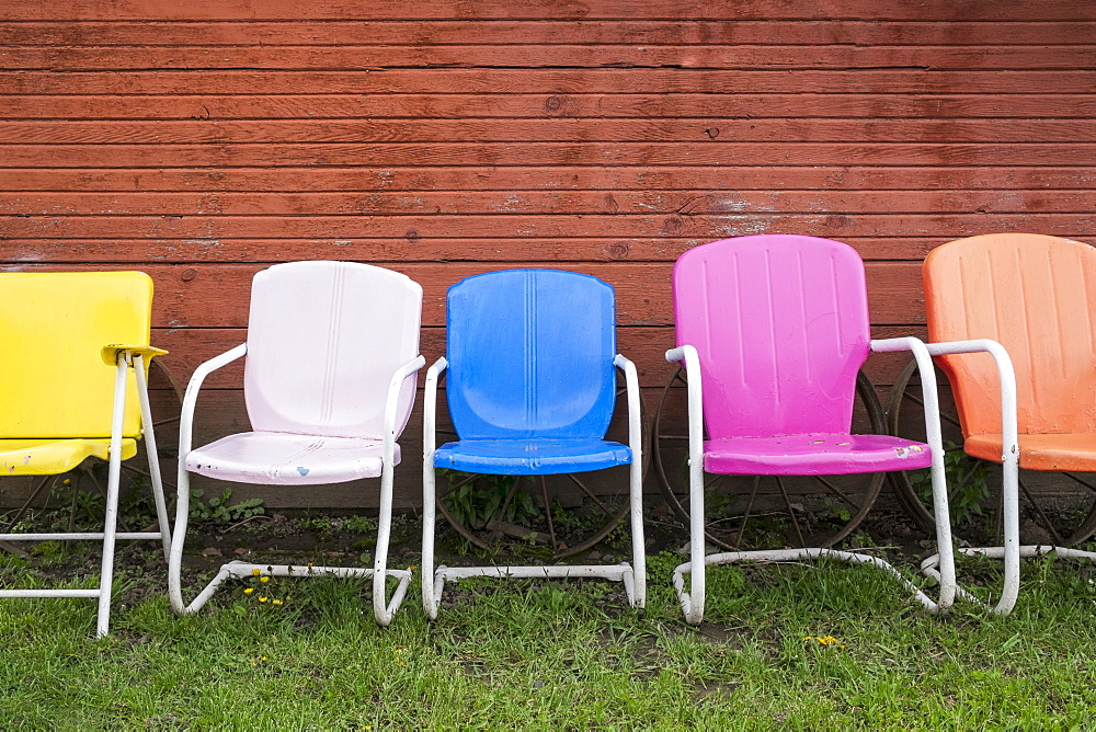 Colorful plastic chairs in row against red wall, Hood River, Oregon