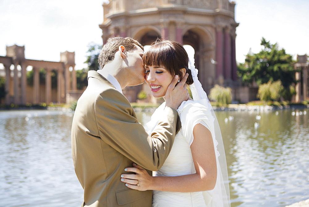 Groom kissing bride in park, San Francisco, California