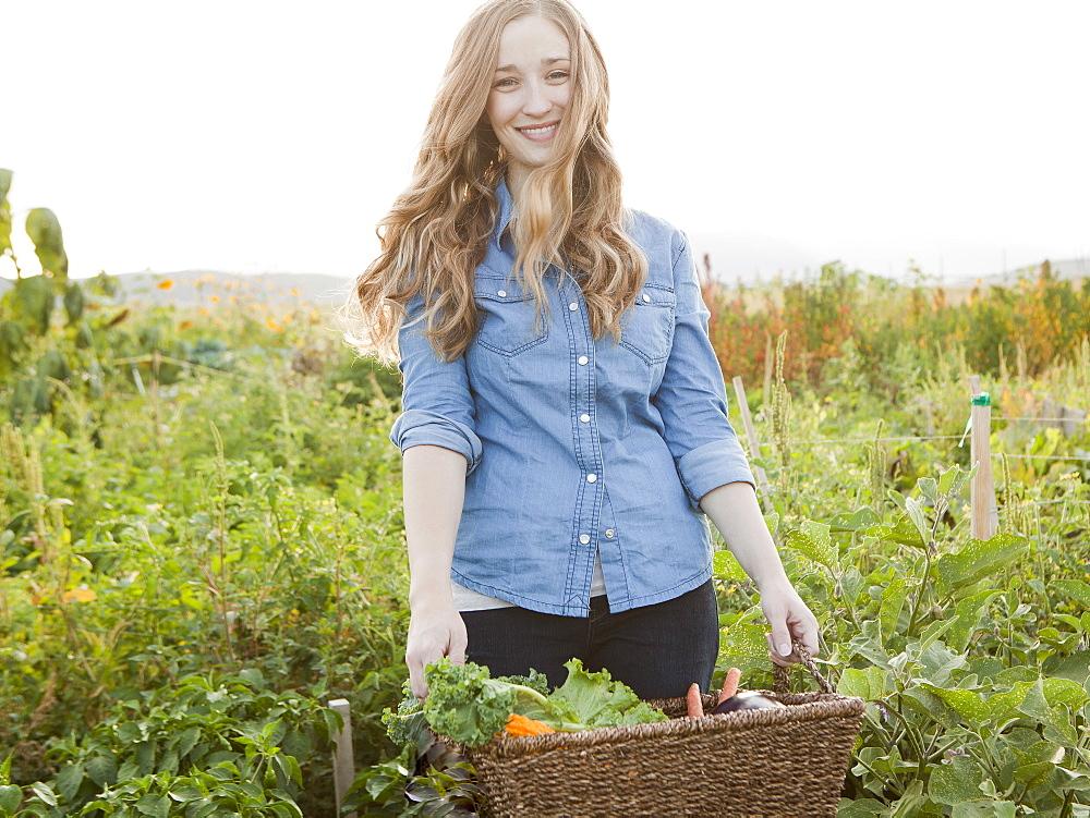 Portrait of young woman harvesting vegetables, Salt Lake City, Utah