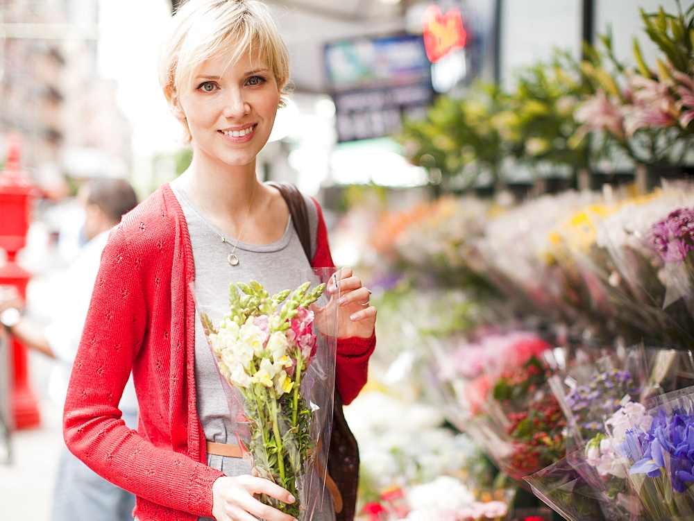 Portrait of smiling woman holding bunch of flowers outside of florist shop, USA, New York State, New York