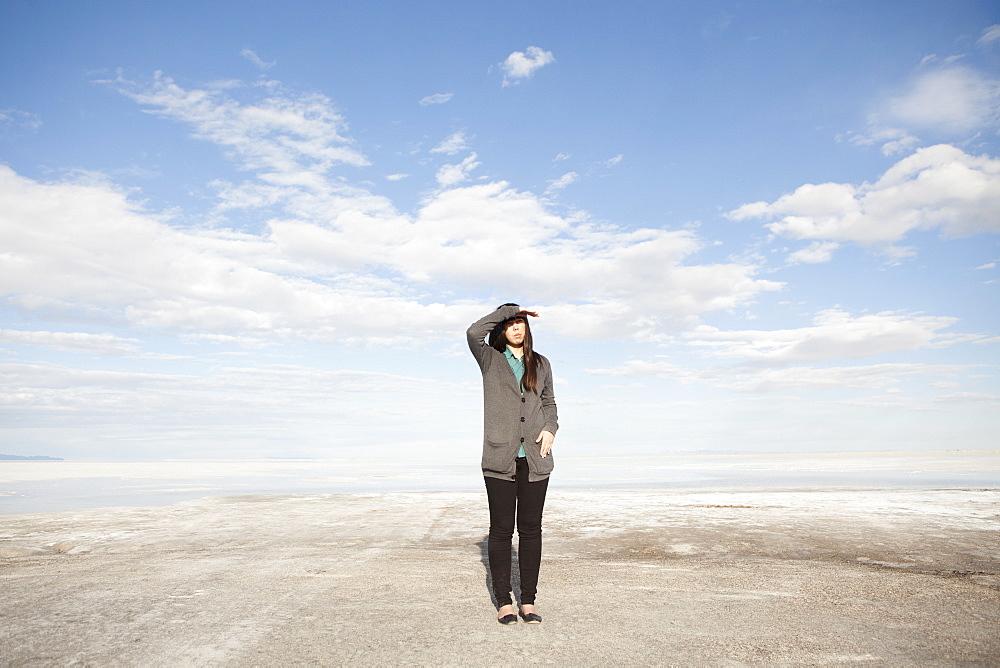 USA, Utah, Salt Lake City, Young woman standing on desert and looking away, USA, Utah, Salt Lake City