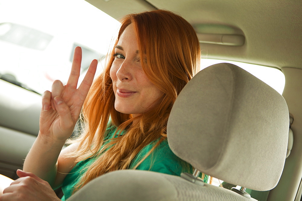 Young woman looking over shoulder and making peace sign
