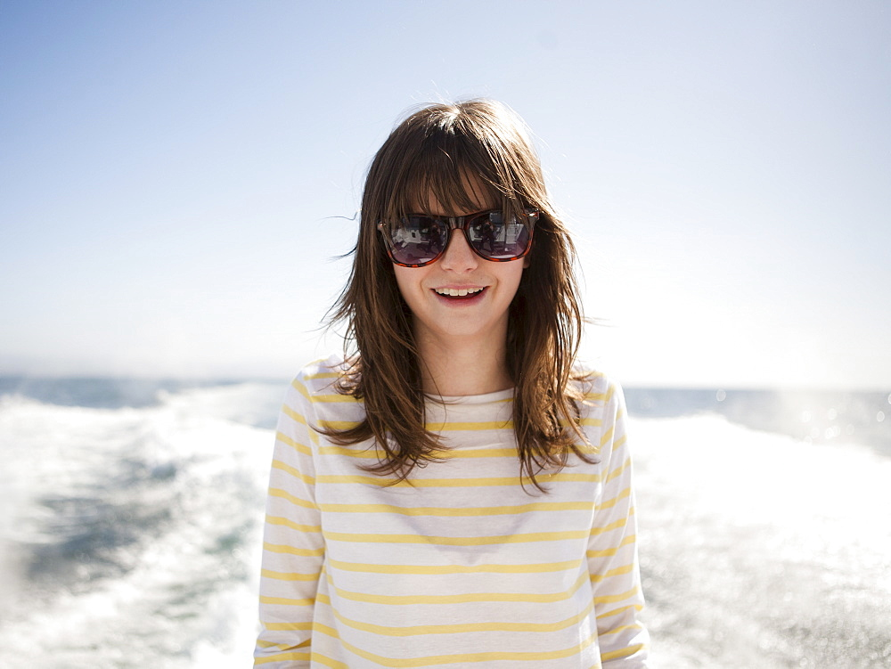 Portrait of young woman in sunglasses in front of sea
