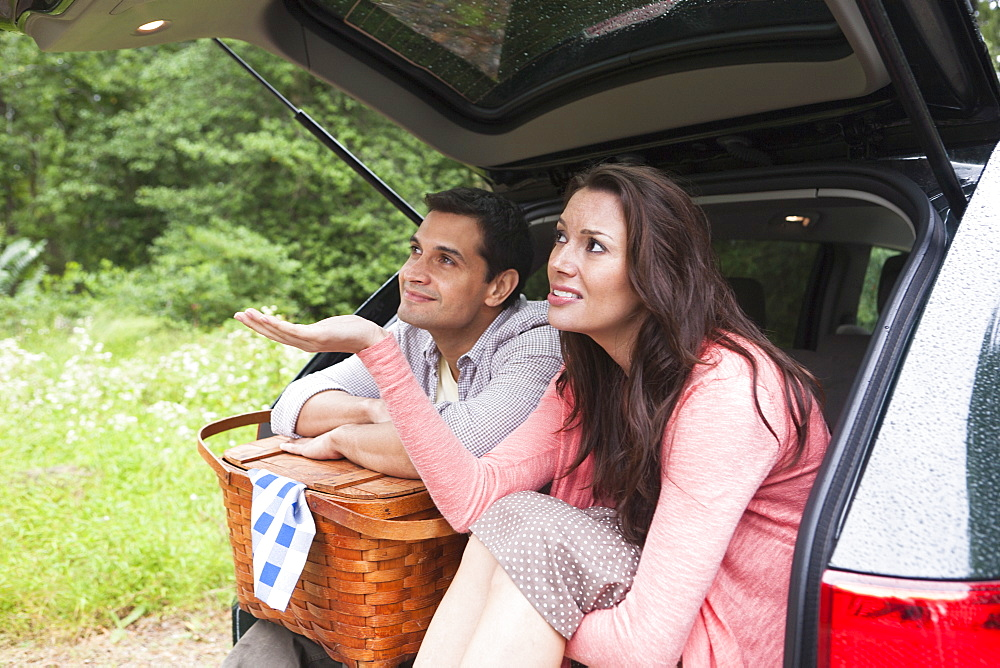 Couple with picnic basket sitting in car trunk