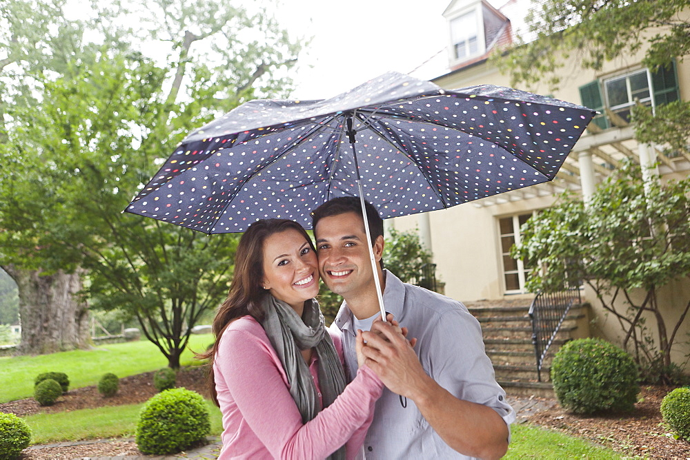 USA, New Jersey, Portrait of couple holding umbrella