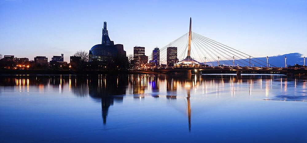 Illuminated skyline reflecting in calm Assiniboine River, Winnipeg Manitoba, Canada