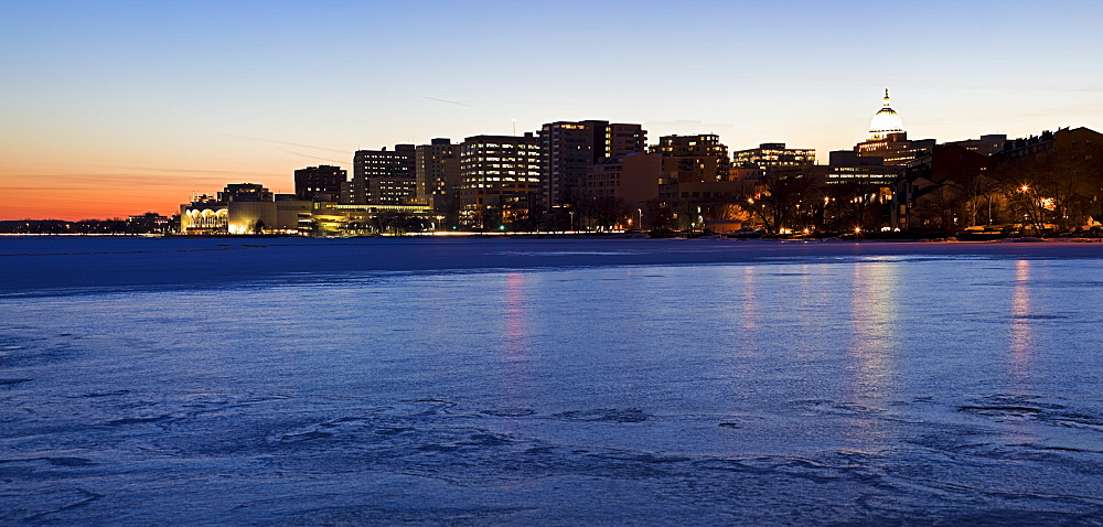 USA, Wisconsin, Madison skyline across frozen lake at dusk