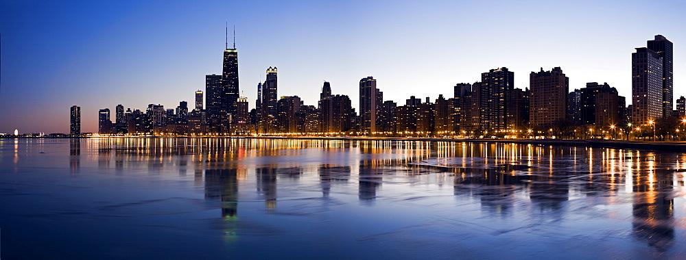 USA, Illinois, Chicago, City skyline over Lake Michigan at sunset