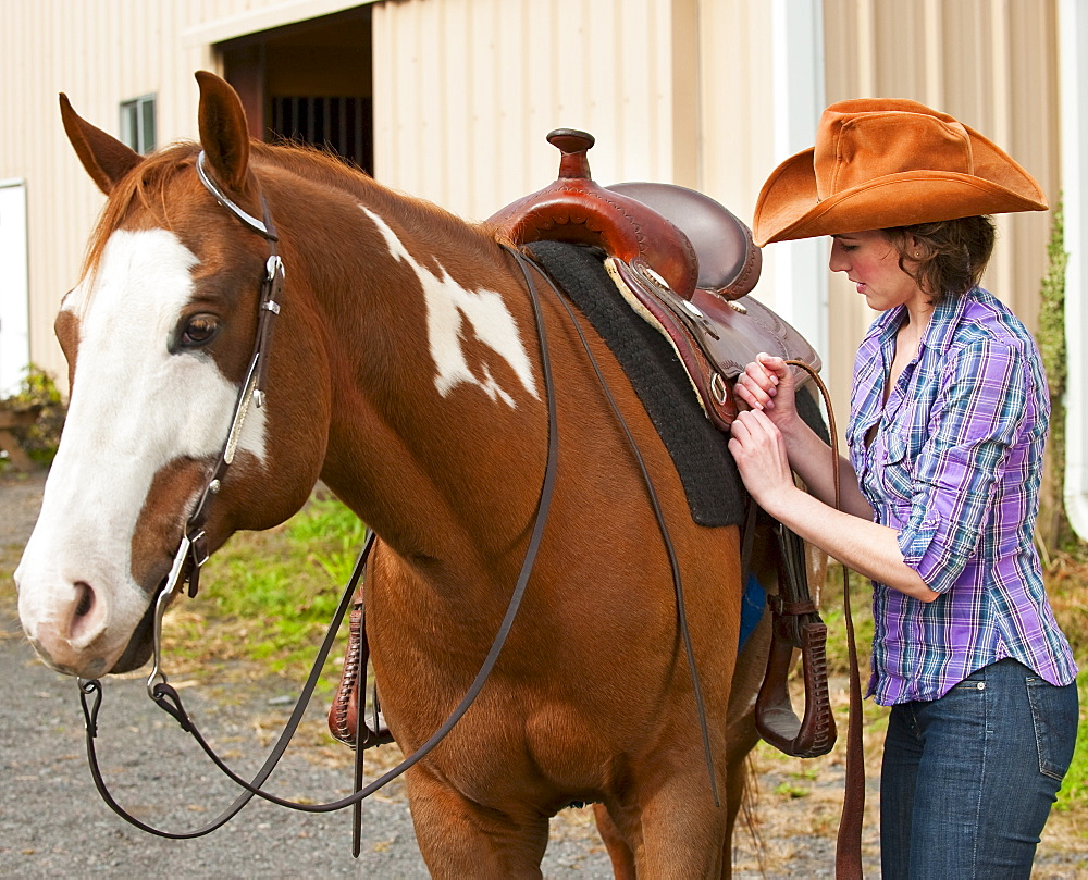 Woman putting saddle on horse