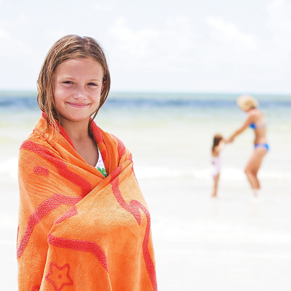 Girl wrapped in towel on beach