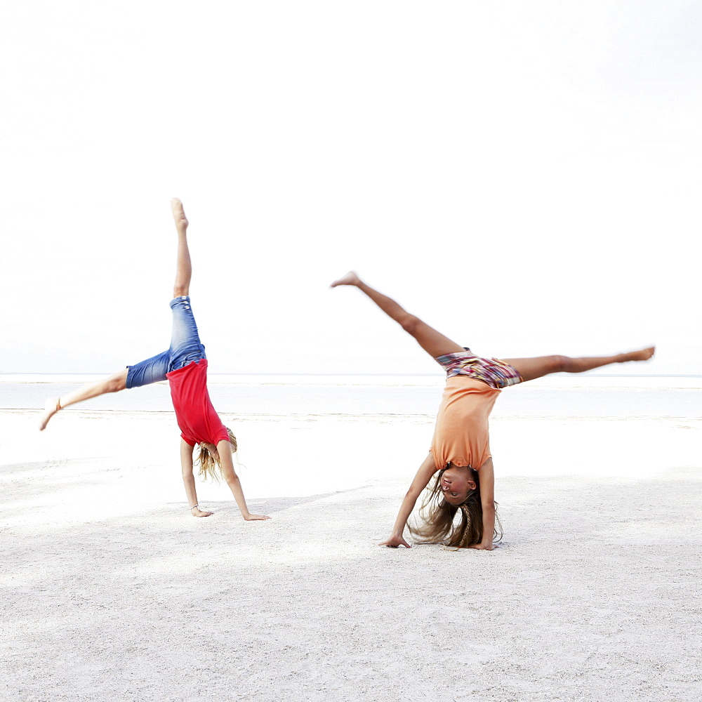 Girls doing cartwheels on beach
