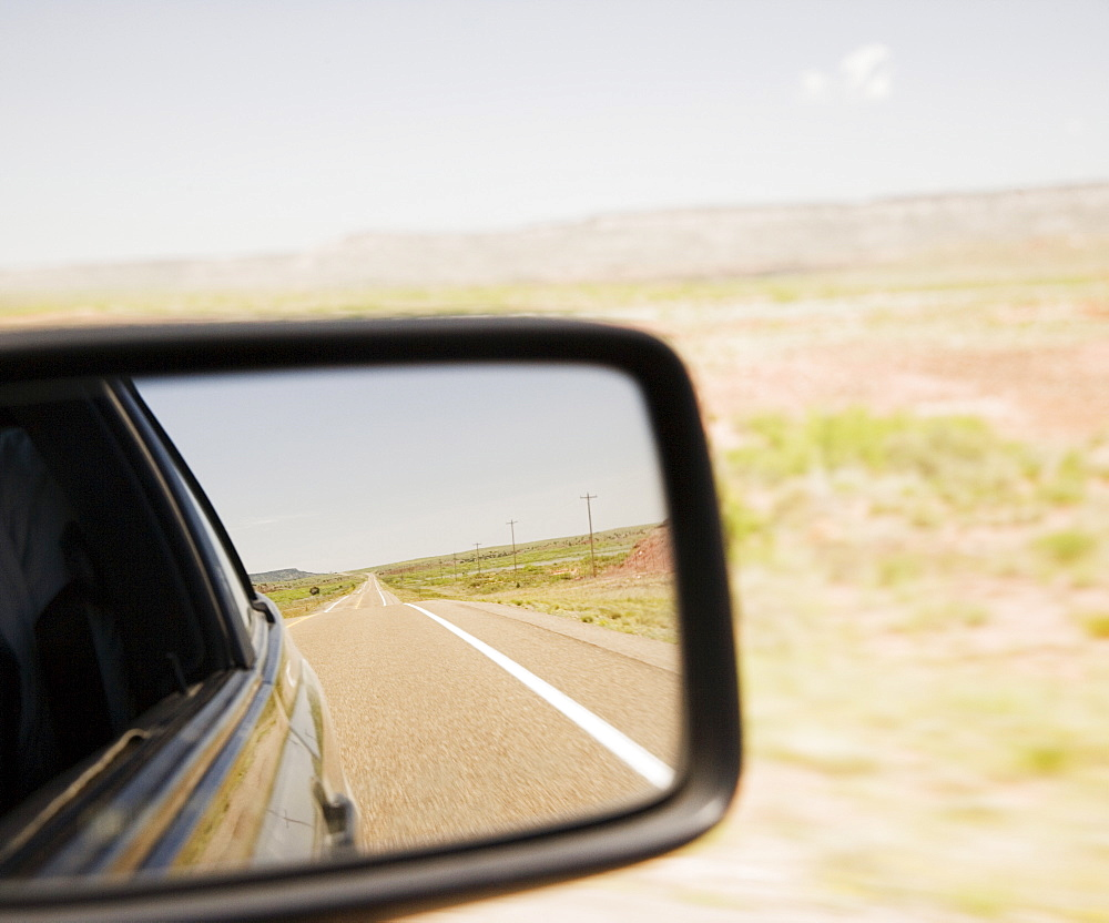 Road reflected in car side mirror