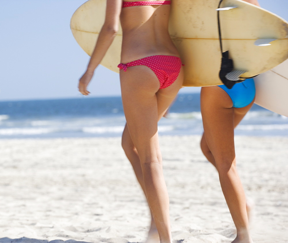 Women in bikinis carrying surfboards