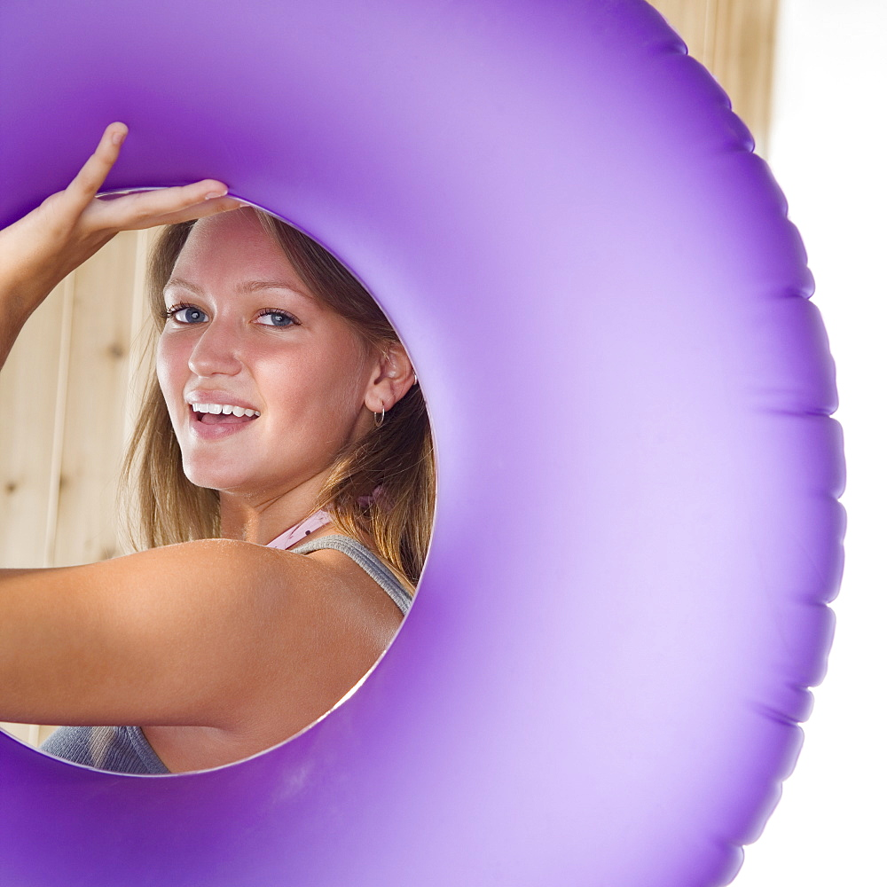 Young woman smiling through middle of inner tube