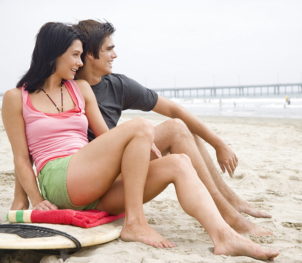 Couple sitting on surfboard at beach