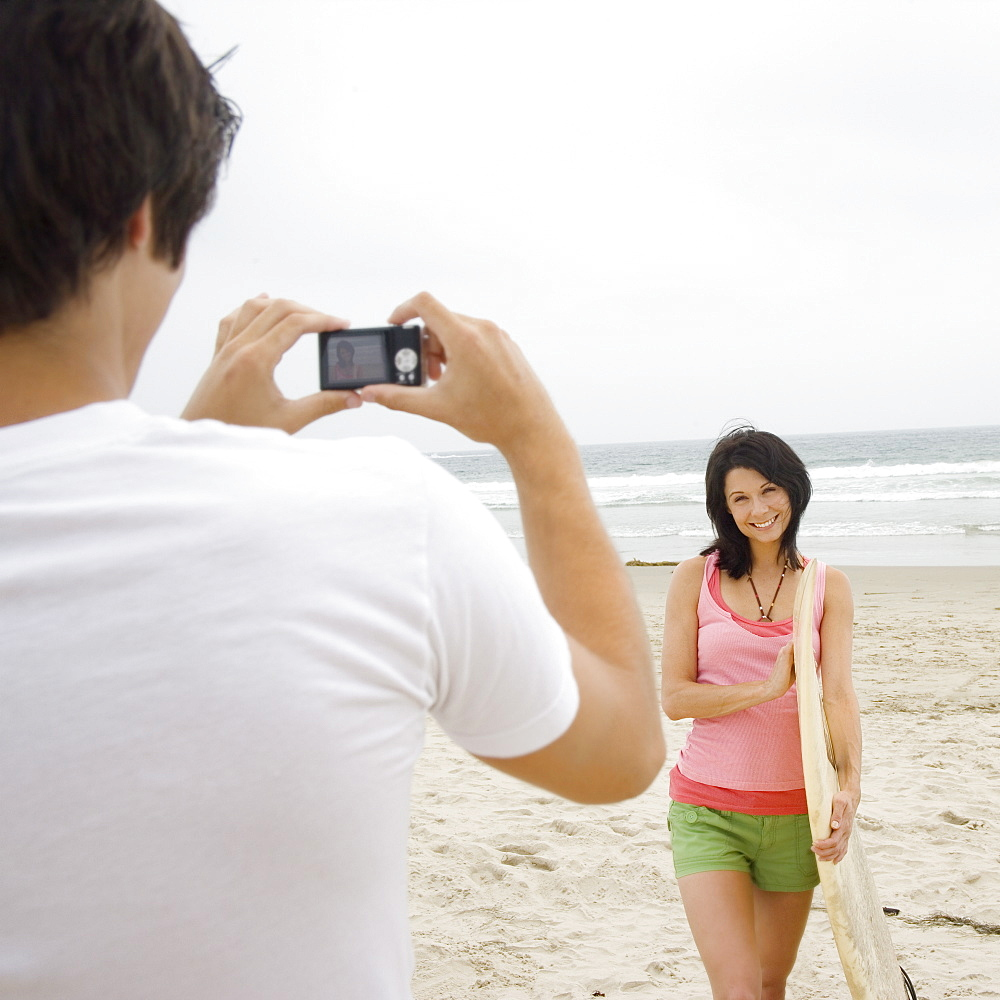 Man taking photograph of girlfriend with surfboard at beach
