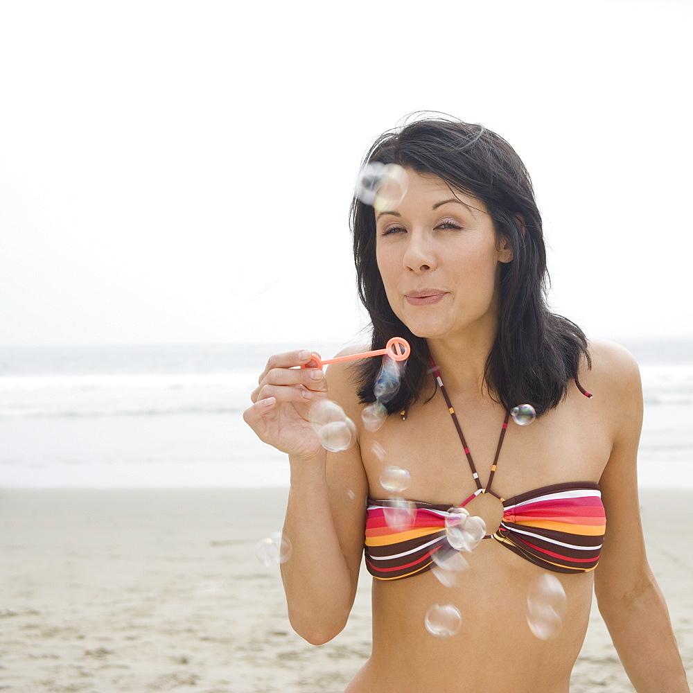 Woman in bikini blowing bubbles at beach