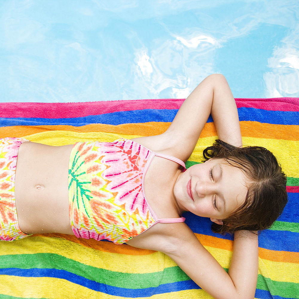 Girl resting on towel at edge of swimming pool