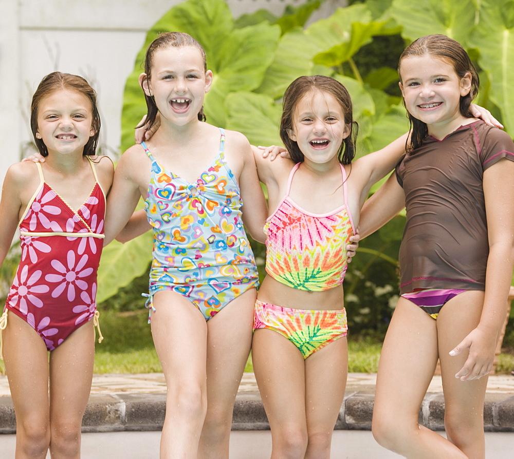 Girls posing by swimming pool