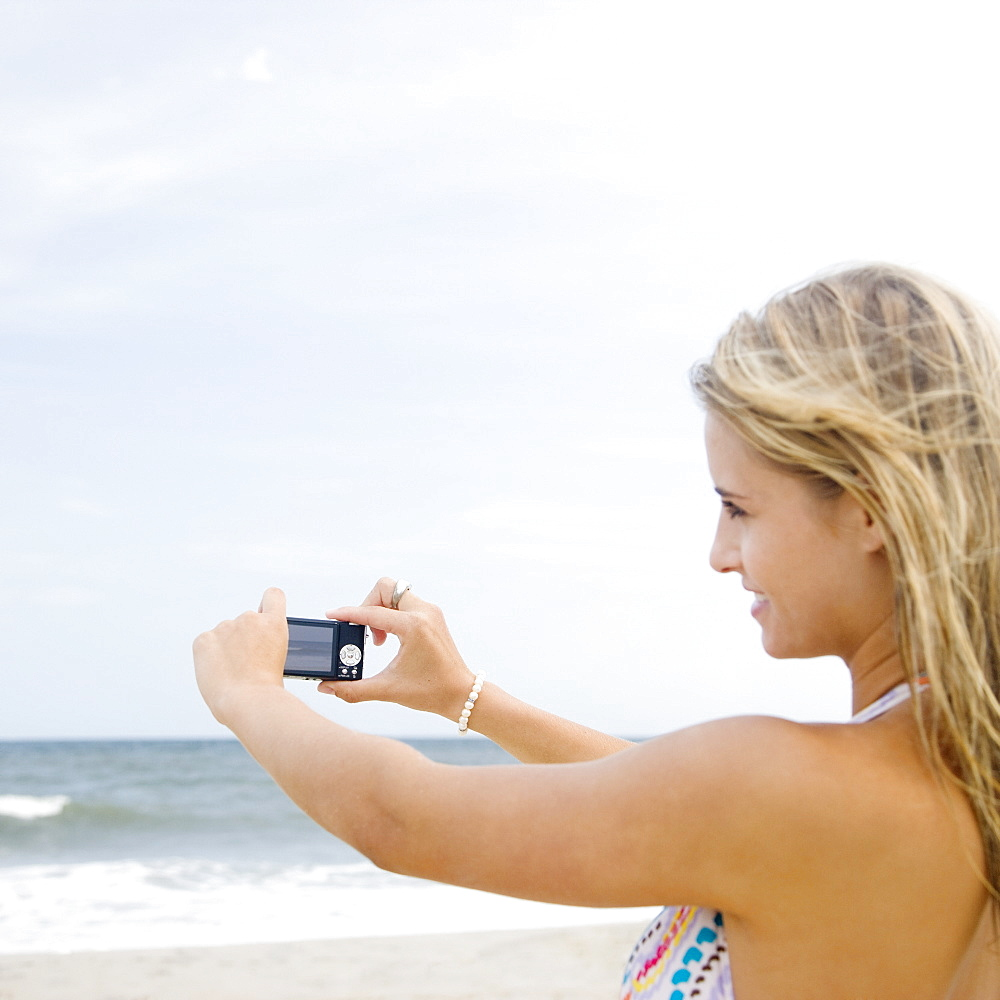 Woman taking photograph of ocean